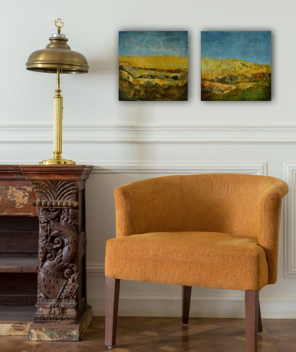 two small impressionist paintings of hills in earthy tones over a chair