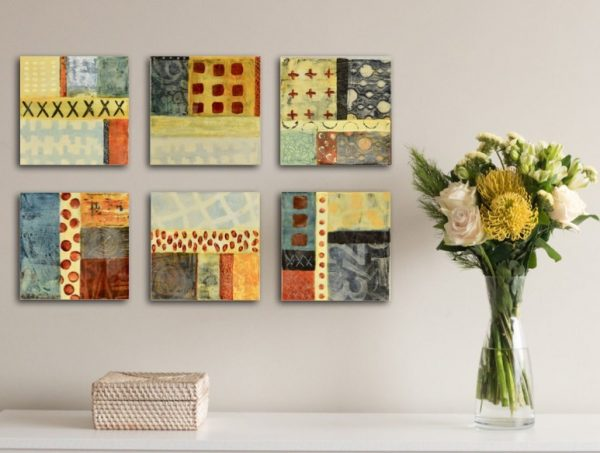 series of six small color block abstract paintings over a table